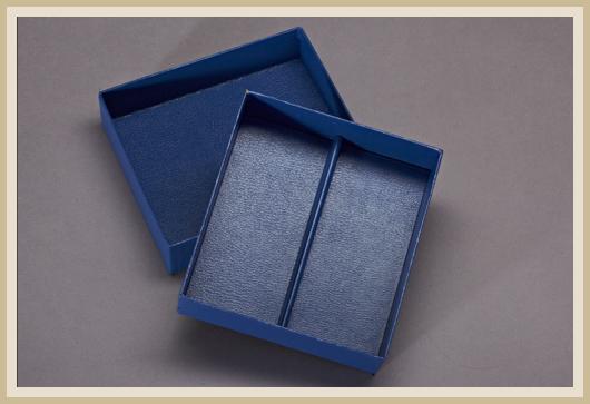Stülpdeckelkarton mit Unterteilung, innen und außen mit Cryluxpapier bezogen.