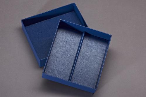 Stülpdeckelkarton mit Unterteilung, innen und außen mit Cryluxpapier bezogen. Mit Deckel.