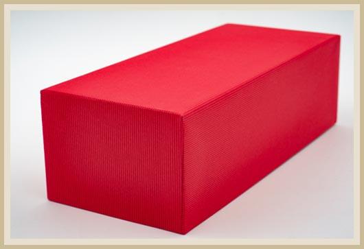 Roter Stülpdeckelkarton mit besonderem Papier bezogen.