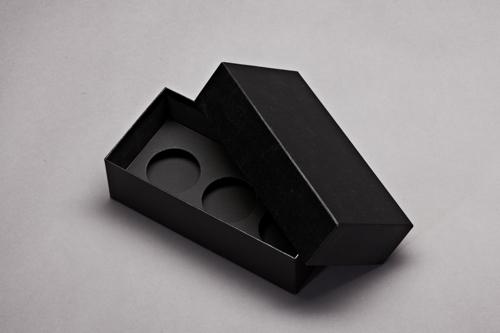 Schwarzer Karton mit Einlage. Zum Beispiel Creme Proben.