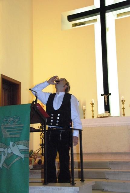 Dachdeckermeister Stefan Meister leert vor dem Richtspruch zum neuen Kirchendach ein Glas Portwein