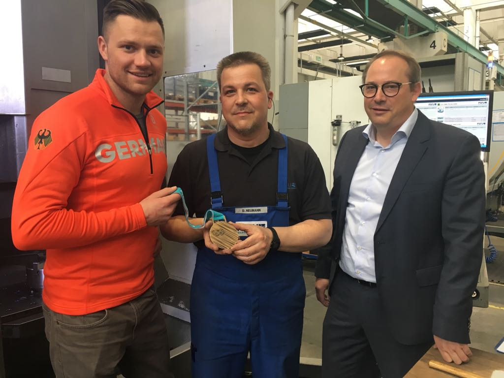 Olympionik samt Medaille zum Anfassen: Rennrodler Toni Eggert bedankt sich bei PSFU-Firmenchef Nils Appelt (rechts) und Dirk Neumann, der stellvertretend für das Team des Wernigeröder Unternehmens steht, das beim Schlittenbau geholfen hat.