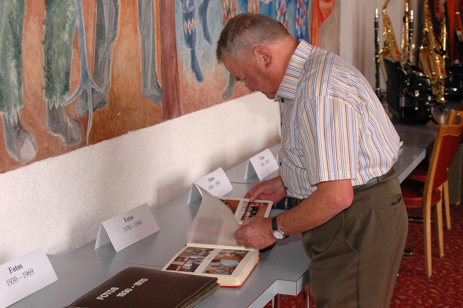 Jean Waltenspühl interessiert sich für die ausgelegten Fotoalben