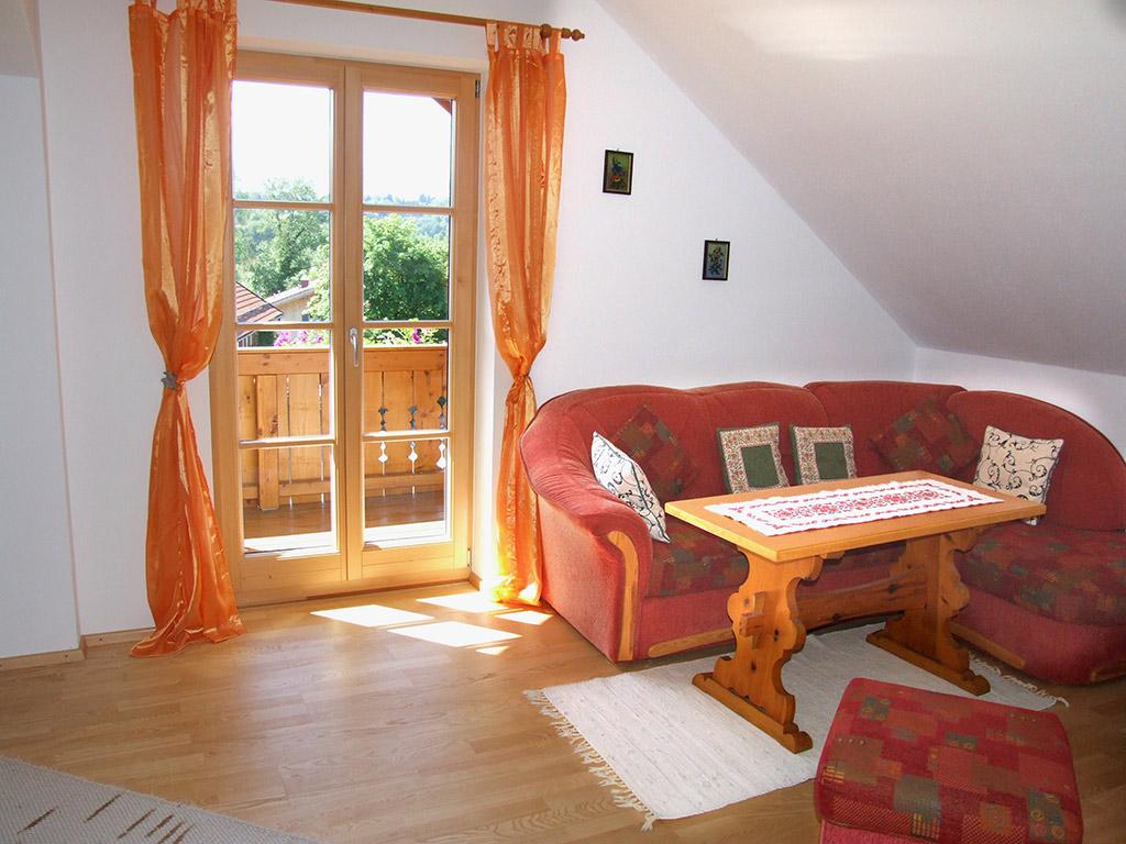 Gemütliche Sitzgruppe im Wohnzimmer (Ausziehcouch für zwei Personen) und einer der drei Ausgänge zum Südbalkon