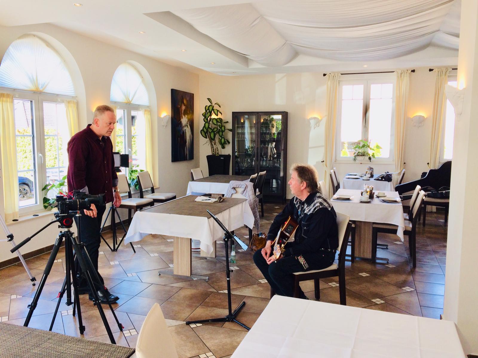 Singer/Songwriter Marcel Schaar stimmt sich auf seiner Gitarre ein und mit Toningenieur Björn Kempcke auf die Technik