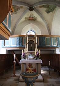 Blick in den Altarraum der St. Johannis-Kirche. Im Vordergrund der Taufstein, der von einer Familie aus Oberscheckenbach gestiftet wurde.