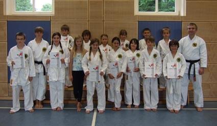 Glückliche Kämpfer des Karate SC Freimann nach der bestandenen Gürtelprüfung mit Sensei Christine Böhmer (2.v.l.) und Prüfer Werner Bachhuber (1.v.r.)
