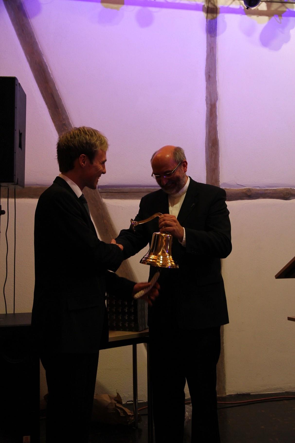 Pfr. Schneider bedankt sich bei Philipp Galm mit einer Mini-Glocke für dessen Engagement