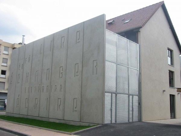 Volume technique (cuisine, vestiaires, chaufferie...): mur en béton brut préfabriqué et engravé ainsi que résille métallique déployée