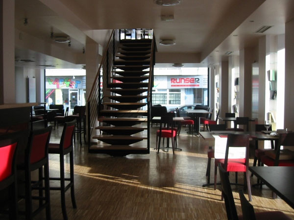Rez-de-chaussée - vue depuis le bar vers l'escalier vers le 1er. A droite de l'image se trouvent des niches de part et d'autre des baies vitrées pour livres, revues