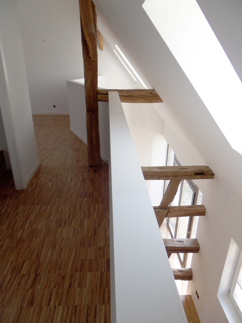 Vue de la coursive depuis l'étage. Le vide permet de créer un volume sur deux niveaux lumineux.