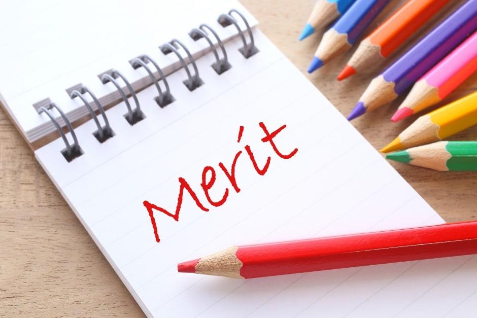 メリットと書かれたメモ帳と赤鉛筆