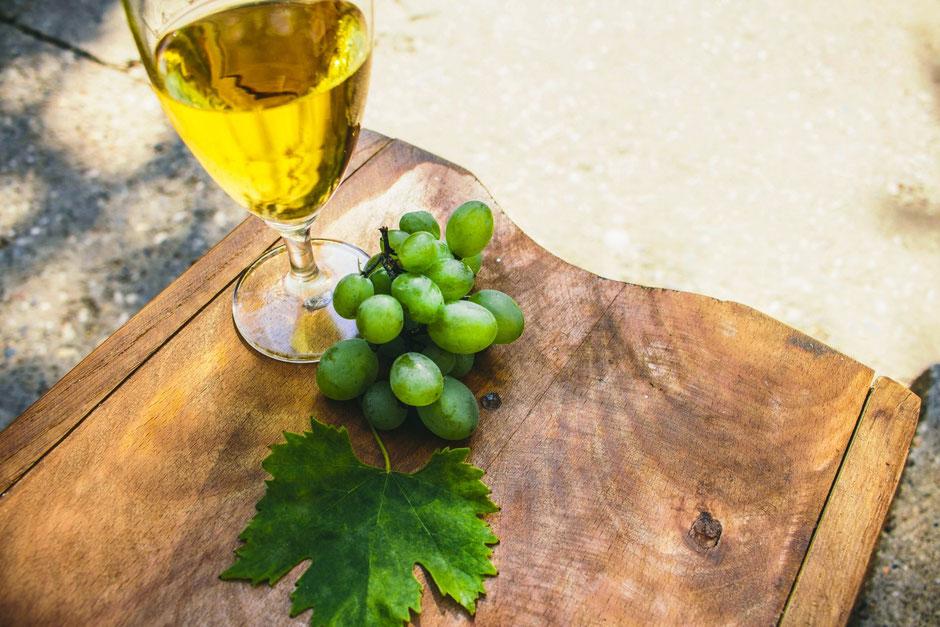テーブルに置かれた白ワインとぶどう