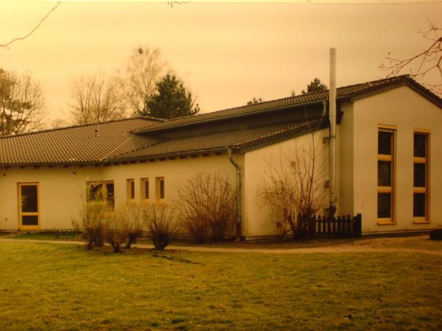 Rückseite des KiGa mit farbig angelegten Holzfenstern, Wärmedämmputz 14cm stark, Gas-Brennwert Kombianlage mit außenliegendem Edelstahlabgasrohr.