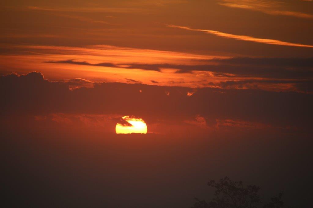 Sonnenaufgang zwischen Wolkenbahnen