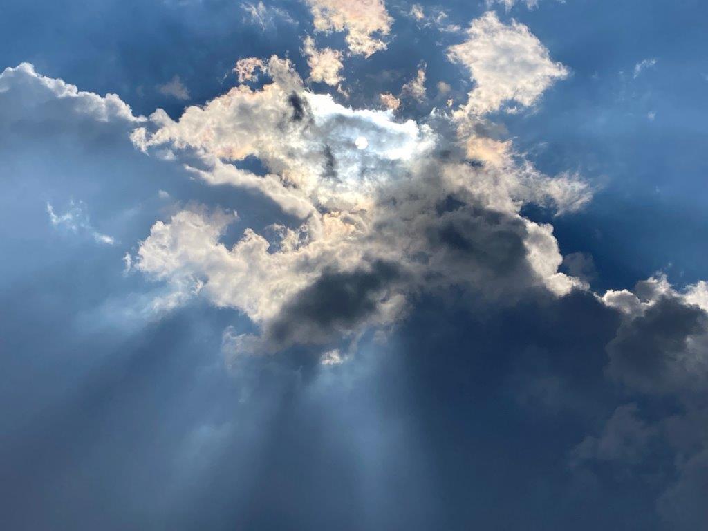 Sonne hinter dramatischem Wolkenfeld