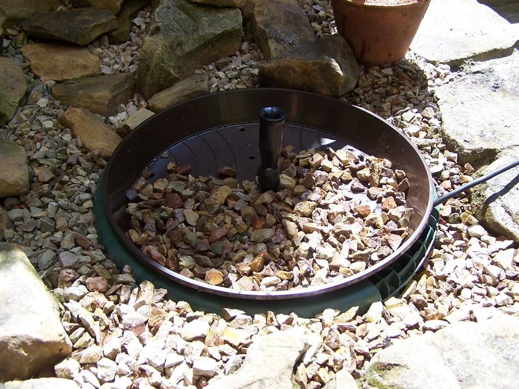 """Durch die Mittelbohrung ragt das Rohr der Wasserfontäne. Steine verzieren den """"Deckel"""".."""