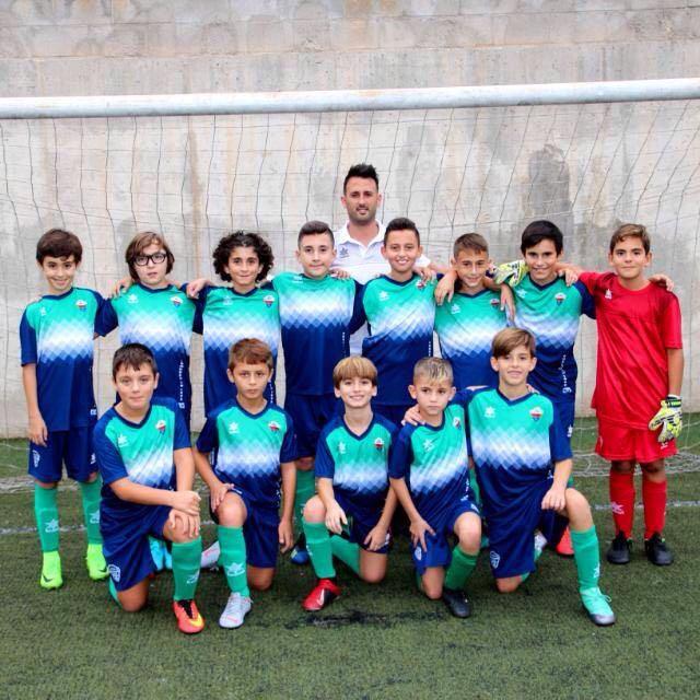 Imagen de 13 niños y el entrenador vestidos con la nueva equipación de su equipo de fútbol. Van con calzas verdes, pantalones azul marino y camiseta azul con el pecho verde y una franja de rombos en color blanco