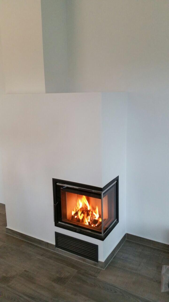 Romantisches Flammenbild im Brennraum des fertig verputzten Eckkamineinsatzes