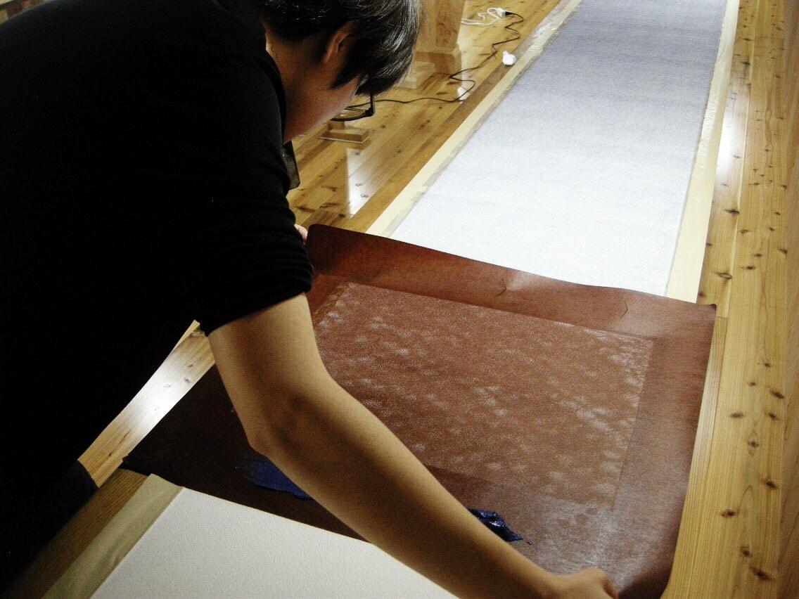 ⦅工程2 型付け⦆型紙にヘラで厚さが均一になるように目糊を置き、送り星を合わせて後ろにつないでいく。一反(約13m)につき約70~90回繰り返す。
