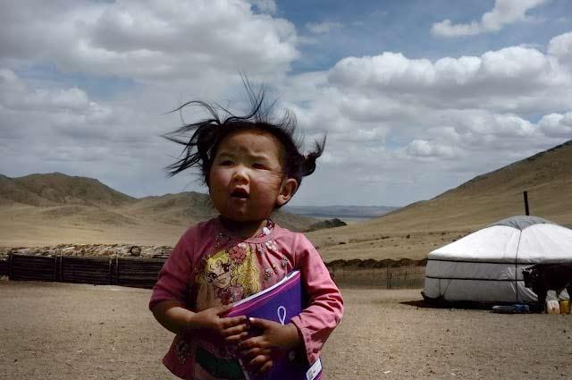 Petite fille devant une yourte dans les steppes de Mongolie