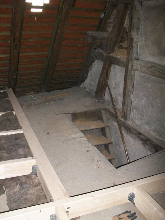 Die Treppe nach unten wird mit einer eine Art hölzerner 'Windfang' isoliert.