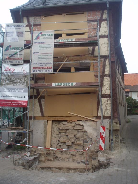 An der Hausfront  werden Vorarbeiten geleistet für das Treppenfundament.