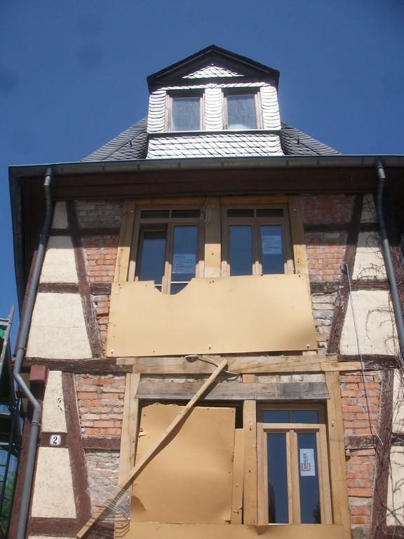 Durch Einsetzen von Fenstern und Eingangstür schließt sich die Front wieder.