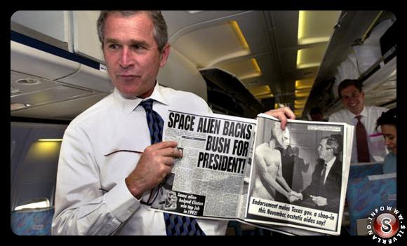 George w. Bush con il giornale che lo raffigura mentre stringe la mano ad un alieno