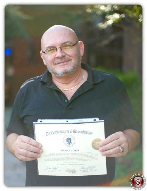 Thom Reed posa per una foto in possesso di un certificato del governatore del Massachusetts che certifica l'avvistamento UFO di Reed