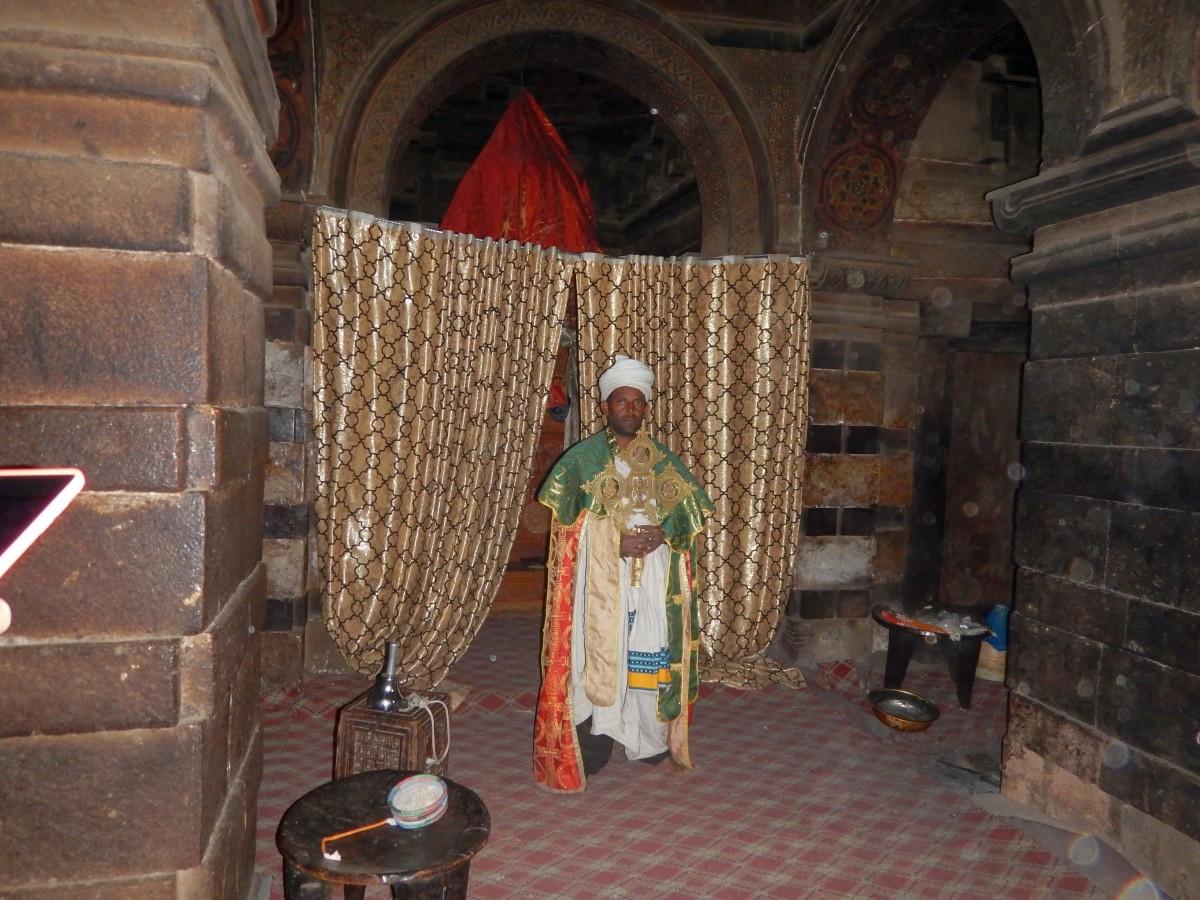 Un moine avec la croix du Prêtre Roi Yemrehanna Kristos. Trek, randonnée à Lalibela en Ethiopie. Visite de l'Eglise Yemrehanna Kristos en Ethiopie.