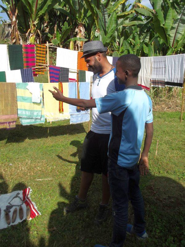 Les écharpes de Dorzé montré par Migbaru, mon fils adoptif et guide éthiopien au travail. Voyage Séjour Trek Trekking Randonnée Road Trip en Ethiopie Visite de la Vallée de l'Omo en Ethiopie. La Ville de Dorze, Le Marché
