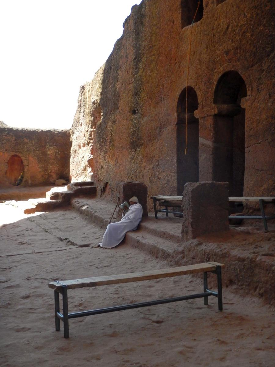 Un moine prie devant Beta Denaghel . Visite de l'église Beta Denaghel de Lalibela en Ethiopie