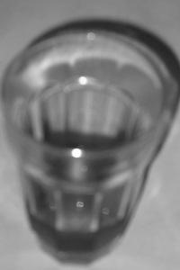 Diese unscharf gestellte Schwarzweißfotografie aus Port Vendres von Thorsten Hülsberg zeigt ein fast leeres Glas.