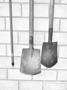 Diese Schwarzweißfotografie von Thorsten Hülsberg zeigt Spaten an einer Wand.