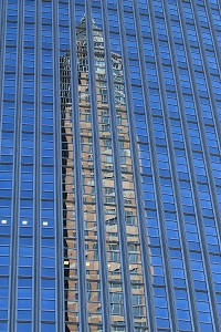 Diese Farbfotografie von Thorsten Hülsberg zeigt den Messeturm in Frankfurt am Main gespiegelt in einer Glasfassade.