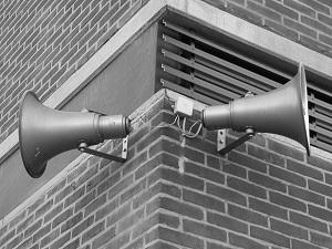 Diese Schwarzweißfotografie von Thorsten Hülsberg zeigt zwei gegeneinander ausgerichtete Lautsprecher an einer Gebäudeecke in Jülich.