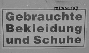 Dieser Fotoausschnitt in schwarzweiß von Thorsten Hülsberg zeigt einen Aufkleber mit der Aufschrift: `Gebrauchte Bekleidung und Schuhe` darüber ist missing gesprayt.