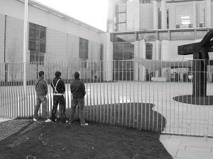 Diese Fotografie von Thorsten Hülsberg zeigt im Videostil drei Jungs am Zaun des Kanzleramts in Berlin und es mutet an, dass sie pinkeln.