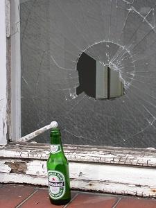Diese Farbfotografie von Thorsten Hülsberg zeigt eine leere Flasche Heineken vor einer zerstörten Fensterscheibe.
