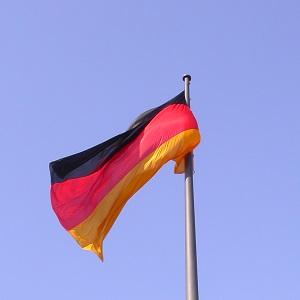 Die Farbfotografie von Thorsten Hülsberg zeigt eine wehende Deutschlandfahne vor blauem Himmel.