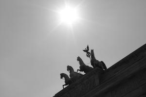 Diese Schwarzweißfotografie von Thorsten Hülsberg zeigt die Quadriga auf dem Brandenburger Tor in Berlin mit strahlender Sonne im Hintergrund.