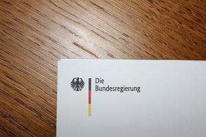 Diese Farbfotografie von Thorsten Hülsberg zeigt den Briefkopf der Bundesregierung auf einem Holztisch.