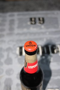 Dieses Farbfoto von Thorsten Hülsberg zeigt eine geschlossene Flasche Union Pils auf einem künstlerisch bearbeiteten Couchtisch.