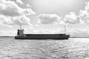 Diese Schwarzweißfotografie von Thorsten Hülsberg zeigt ein Frachtschiff auf der Elbe.