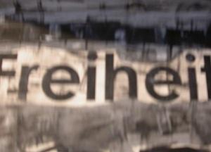 Dieser Fotoausschnitt von Thorsten Hülsberg zeigt etwas verschwommen einen Teil eines in schwarzweiß und grau gehaltenes Werkes aus der GRAUzone, welches etwas abgeschnitten das Wort Freiheit zeigt.