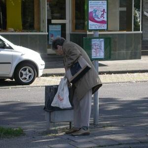 Dieses quadratische Farbfoto von Thorsten Hülsberg zeigt eine ältere Frau, die an einem Busbahnhof den Müll durchsucht.