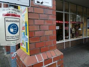 Diese Farbfotografie von Thorsten Hülsberg zeigt ein Schild zur Maskenpflicht, wo dahinter ein Laden dicht macht.