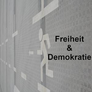 Diese Schwarzweißbild von Thorsten Hülsberg zeigt ein Fluchtpiktogramm und hinter der flüchtenden Person steht in schwarz Demokratie & Freiheit.