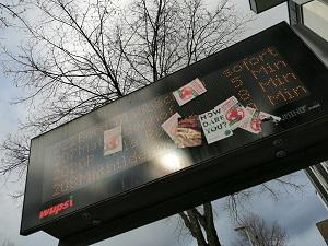 Dieses Farbfoto von Thorsten Hülsberg zeigt eine Busabfahrtsanzeigetafel in Leverkusen, welche weitestgehend mit Stickern von Klimaaktivisten zugeklebt wurde.